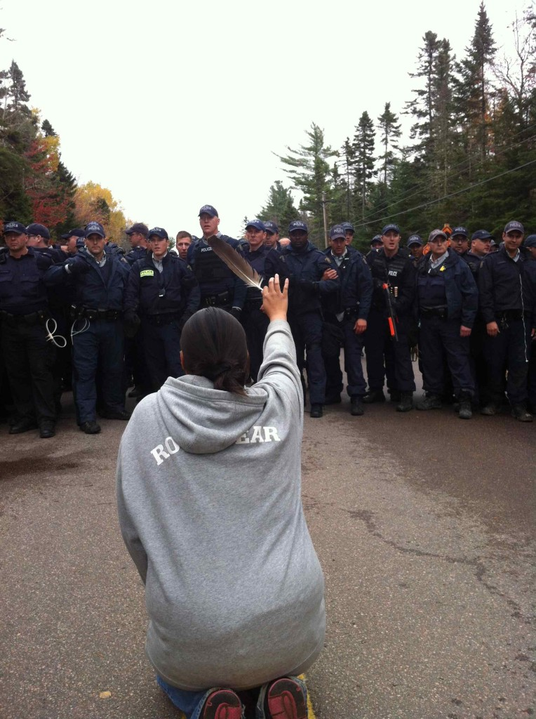 Amanda Polchies, a Mi'kmaq woman, faces RCMP riot police on Oct. 17, 2013, in Rexton, New Brunswick. (Photo by Ossie Michelin/APTN National News)